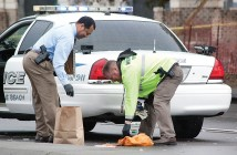 Staff photo by Emmy Errante. Officers gather piles of money off Wrightsville Avenue around 10:30 a.m. Monday, March 23.