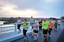 Staff photo by Emmy Errante. Runners cross the Heide Trask Drawbridge as the sun rises during the Wrightsville Beach Marathon Sunday, March 22.