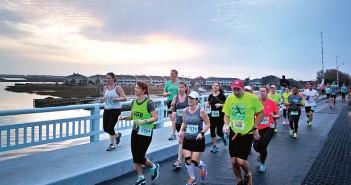 Staff photo by Emmy Errante. Runners cross the Heide Trask Drawbridge as the sun rises during the Wrightsville Beach Marathon Sunday, March 22.
