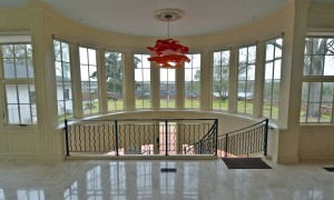 Grand circular stair leads from the solarium to the ground level. Wrought iron railings were fabricated by Ben Kastner. Photo courtesy of BMH Architects