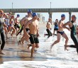 Staff photo by Emmy Errante. Swimmers run into the water near Johnnie Mercer's Pier to begin the Stoked to Go Out Grey Liston memorial swim Saturday, May 16 at Wrightsville Beach.