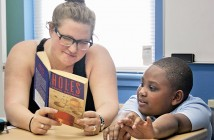 """Staff photo by Emmy Errante. Hillcrest Reading Program tutor Rachel Armstrong listens while seven-year-old Rasu Montgomery reads aloud from the book """"Holes"""" April 21 at the Hillcrest Public Housing community center."""