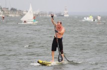 Lumina News file photo. Wilmington resident Eric Carter strokes for the finish line in the Blockade Runner Beach Resort's Sunset Standup Paddleboard series June 5, 2014.
