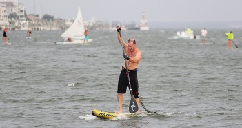 Lumina News file photo. Wilmington resident Eric Carter strokes for the finish line in the Blockade Runner Beach Resort's Sunset Standup Paddleboard series June 5, 2014.