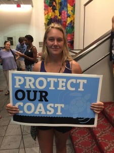 University of North Carolina Wilmington student Allie Ryan holds a sign to protest offshore drilling in North Carolina at a Wilmington City Council meeting July 21.