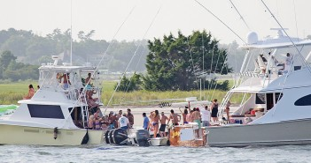 Lumina News file photo. Two sport fishing boats anchored in Banks Channel behind United States Coast Guard Station Wrightsville Beach swap passengers on the Fourth of July, 2014.