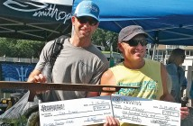 Staff photo by Terry Lane. Ryan McInnis, right, organizer of the Wrightsville Beach Spearfishing Tournament, awards Dre Fleury the title master hunter of the men's division for the second consecutive year Sunday, July 19.