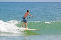 Staff photo by Emmy Errante. A paddleboarder rides a wave Tuesday, Sept. 1 at Wrightsville Beach.