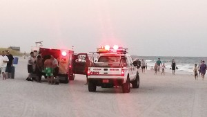 Wrightsville Beach Ocean Rescue tends to four swimmers rescued from a rip current by surfers Trey Lewis and Deaton Wright July 17 north of Johnnie Mercer's Pier.