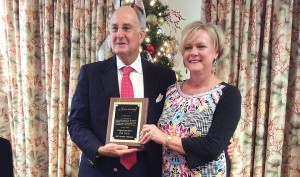 Supplied photo courtesy of the New Hanover County Tourism Development Authority. Kim Hufham, president and CEO of the New Hanover County Tourism Development Authority, presents Republican Rep. Ted Davis with the N.C. Travel & Tourism Coalition Tourism Champion Award on Friday, Dec. 18 at the Holiday Inn in Wrightsville Beach.