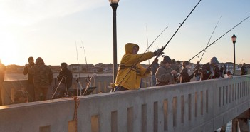 Staff photo by Emmy Errante. A fisherman casts a line as the sun sets during the 11th annual Johnnie Mercer's Pier Dogfish Tournament Saturday, Jan. 30.