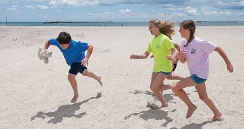 Staff photo by Allison Potter. Wrightsville Beach School students Nellie Harris, right, and Bella Ellison, act as birds chasing a predator, Andrew Warshaw, from their nests during a field trip with Audubon North Carolina Monday, May 23.
