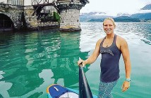 Supplied photo courtesy of April Zilg.  Paddleboarder April Zilg snaps a photo of herself by Oberhofen Castle in Lake Thoune, Switzerland, on June 1 in between races in Europe. Zilg competed in four races on the EuroTour in May and June, helping her advance into the worldwide top 10 for standup paddleboard racers.