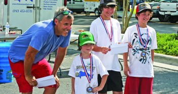 James Hurley, 9, far right, and brother Owen, 11, with father Gary Hurley, left, after winning the Pre-teen Angler award at the Wide Open Tech Spanish Mackerel Tournament on Sunday, Aug. 21. Staff photo by Terry Lane .