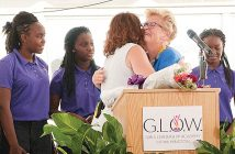 Staff photo by Allison Potter. Students at the Girls Leadership Academy of Wilmington look on as G.L.O.W. principal Laura Hunter, left, and G.L.O.W. founder Judy Girard hug during the school's grand opening ceremony Monday, Aug. 29. G.L.O.W. is the first single-gender public charter school in North Carolina.