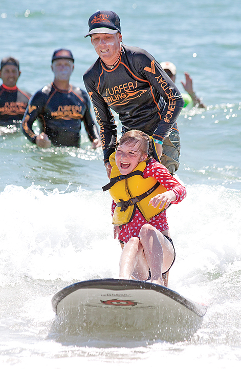Staff photo by Emmy Errante. Volunteers with Surfers Healing take people with autism surfing at Wrightsville Beach Aug. 22.