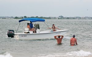 Lumina News file photo. A man pleads for a ride from a boater on Masonboro Island as Independence Day 2016 partying wraps up.